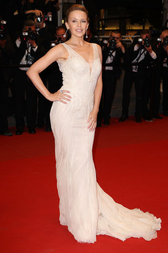 Kylie Minogue posed confidently in her plunging neutral Roberto Cavalli gown and Chopard drop earrings at the Les Saludes premiere at Cannes.
