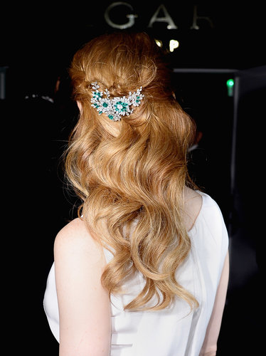 And she embellished her half-up hairstyle with an emerald and diamond broach.