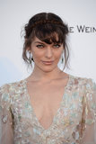 Milla Jovovich wore face-framing tendrils and a headband braid for her appearance on the amfAR red carpet.