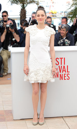 Marion Cotillard showed off her panache in a white Alexander McQueen 3D flower-embroidered dress and embellished pumps at the Immigrant photocall at Cannes.