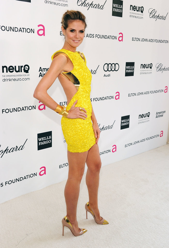 In true supermodel fashion, Heidi struck a fierce pose in a bright yellow, backless, futuristic Atelier Versace minidress with metallic trim. As if her mini wasn't showstopping enough, the model slipped on a pair of cap-toe Christian Louboutins to really seal the deal.