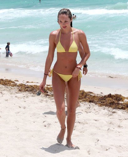 Candice Swanepoel's beach look popped with her bright yellow halter bikini and colorful beaded bracelets after a swim in Miami.