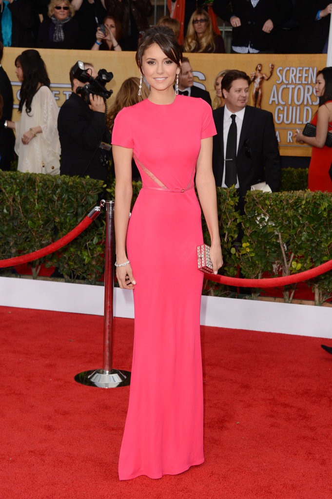 Nina Dobrev punched up the 2013 SAG Awards red carpet in a pink short-sleeved Elie Saab crepe creation with subtle lace cutouts and a matching belt. A diamond drop earrings, a coordinating bracelet, and a jeweled box clutch rounded out her party style.