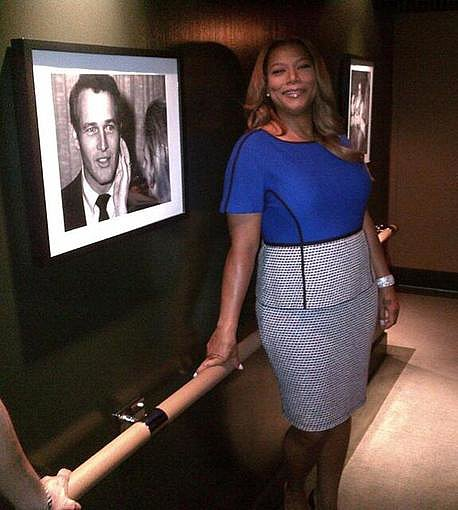 Queen Latifah posed near a photo of Paul Newman before doing some press in Canada. So