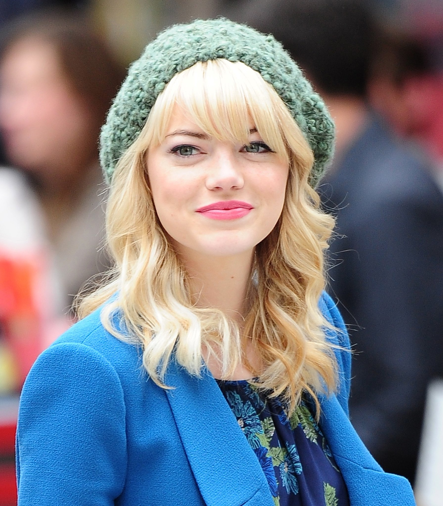 Wavy hair and bangs are an alluring combination on Emma Stone.