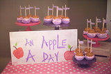"""With all the candy from the pharmacy and sweets on the dessert table, we thought we'd offer our guests some fruit,"" Jenny said. ""So we did an 'Apple a Day' table filled with purple and pink chocolate-dipped caramel apples. Source: Jenny Cookies"