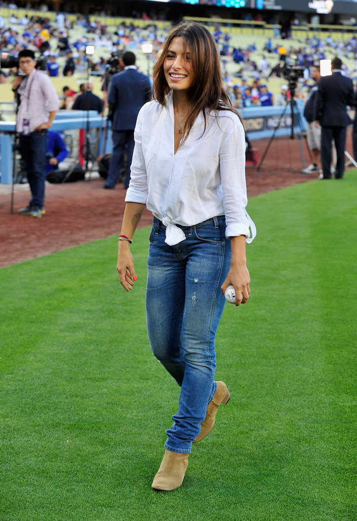 Actress Sarah Shahi picked an all-American ensemble to throw out the first pitch at Dodger Stadium, pairing classic blue jeans with Isabel Marant boots and a white button-up knotted at the waist.