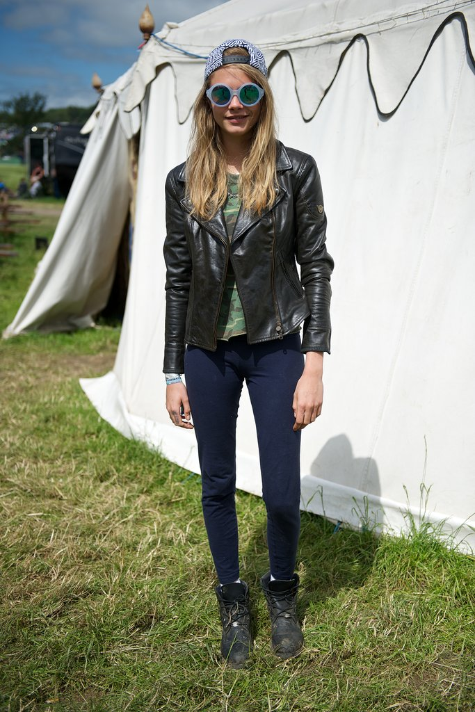 Cara Delevingne sported a backwards baseball cap with funky round sunglasses, and a camouflage tee at Glastonbury.