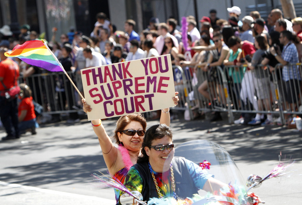 Revelers during the San Francisco Gay Pride Parade held up signs in favor of the Supreme Court's recent rulings.