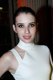 Emma Roberts kept things incredibly sophisticated with a pulled-back bun, thick black liner, and a muted rose lip color at Versace.