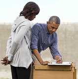 First Lady Michelle Obama looked on as President Obama signed a guest book in the Robben Island prison yard outside Cape Town, South Africa, in June.
