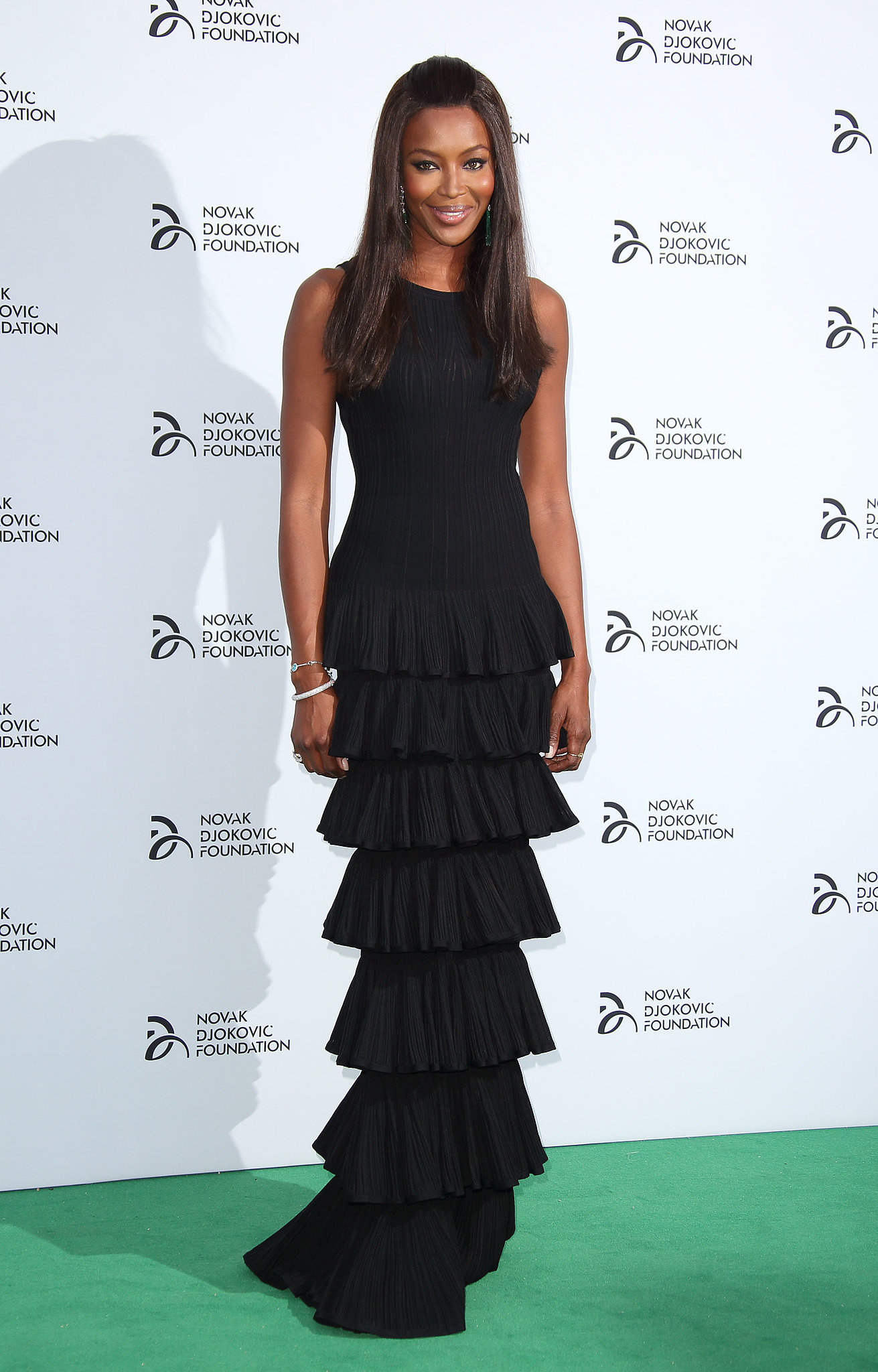 At the Novak Djokovic Foundation dinner, Naomi Campbell made an entrance in a tiered, black column gown.