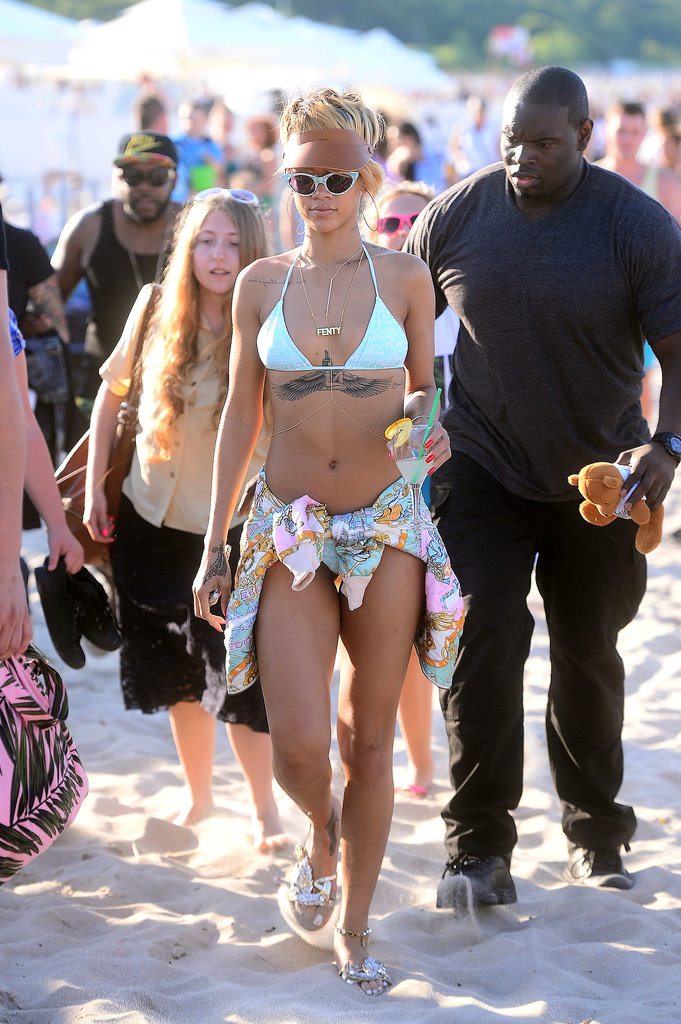 Rihanna flashed her toned abs and large tattoo as she strolled along a beach in Poland in a bikini on July 7.