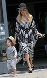 Rachel Zoe ran around with Skyler at the Malibu Country Mart looking bohemian in a black-and-white Theodora & Callum caftan, a black wide-brim hat, chunky gold necklace, round sunglasses, and black wedges.