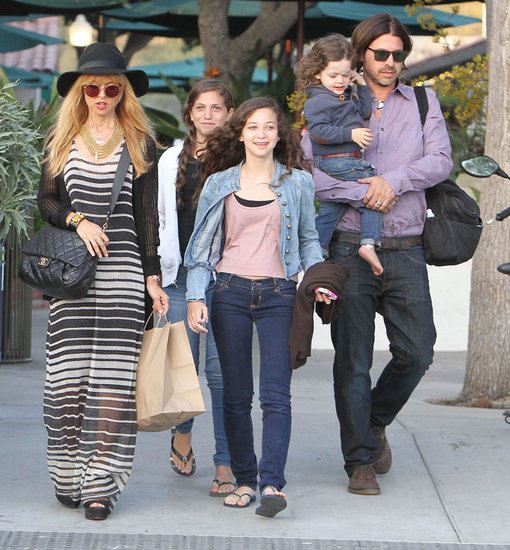 During a family outing, Rachel Zoe stood out in a sheer striped maxi dress. A black cardigan, black hat, quilted Chanel bag, and wedge sandals completed her SoCal style.