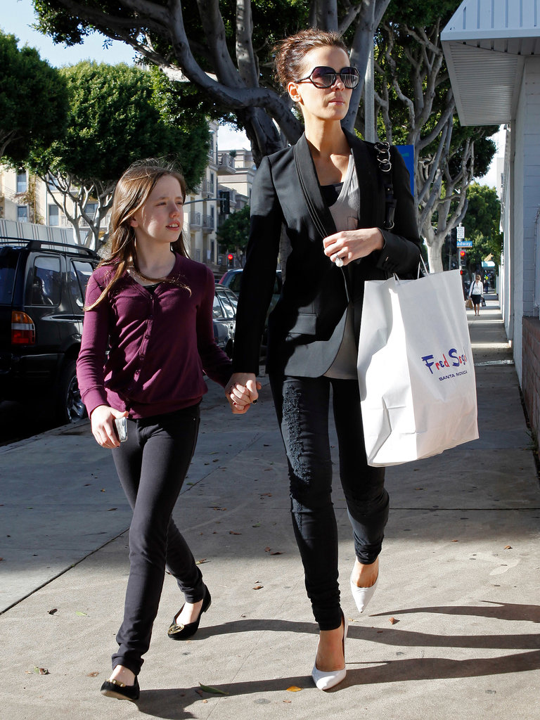 Kate styled black scroll-embroidered jeans with a smart blazer and white pointed pumps while shopping with her daughter, Lily, in 2009.