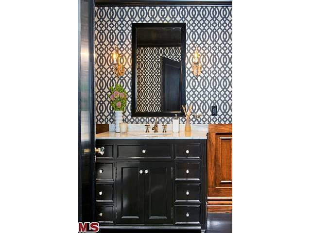 A charcoal trellis pattern on the walls helps to modernizes the wooden wainscoting.