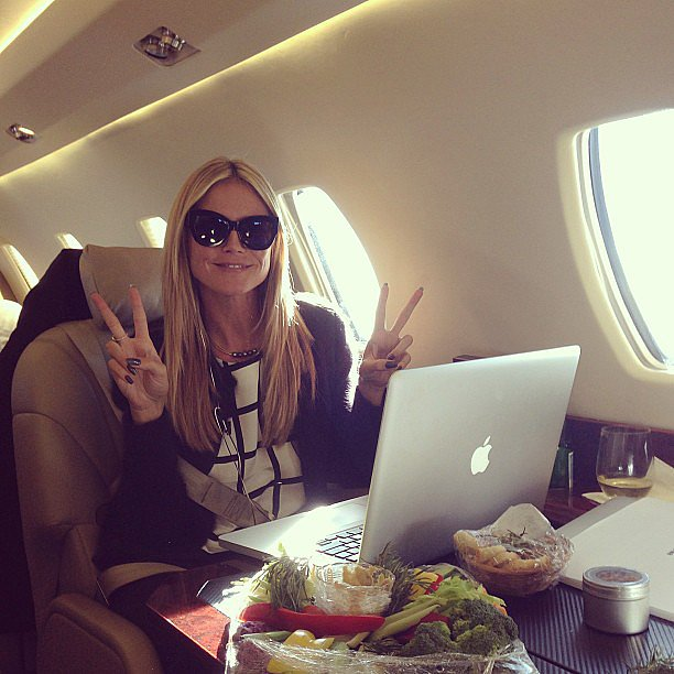 Heidi Klum flashed double peace signs during a flight to NYC. Source: Instagr
