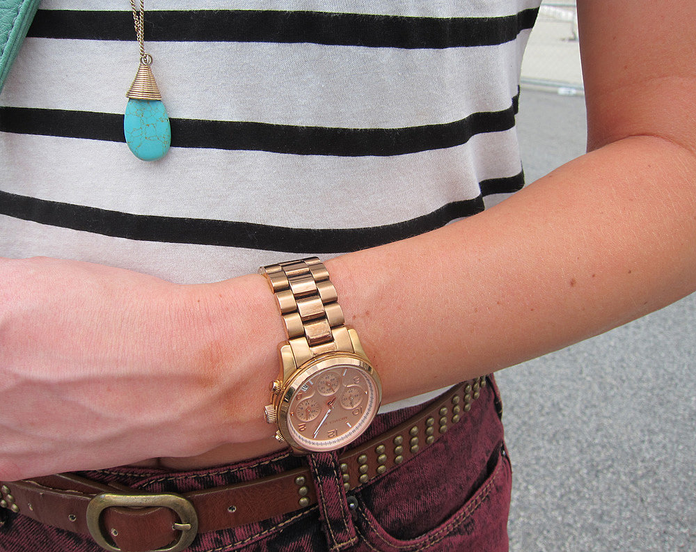 So many concerts, so little time. We'd happily stay on schedule with her gold Michael Kors watch, which complements this turquoise pendant necklace.