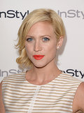 A chignon and a bright tangerine lipstick color made for a sweet combo on Brittany Snow.