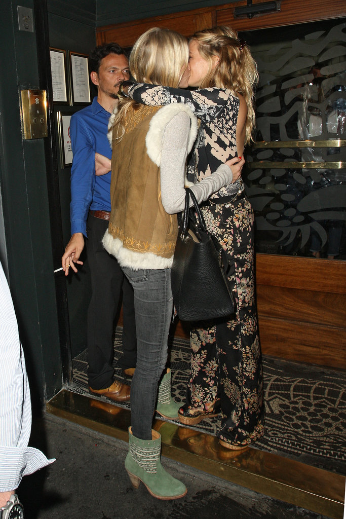 Sienna Miller gave her pal Poppy Delevingne a friendly kiss during a night out in London.