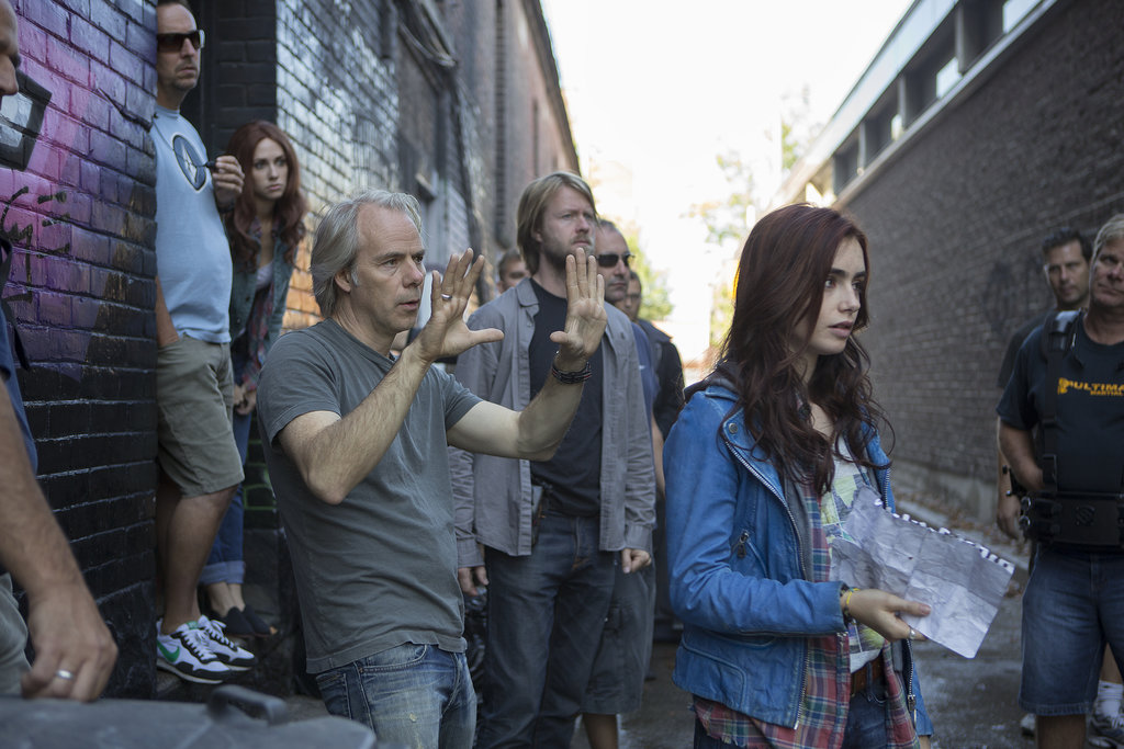 Director Harald Zwart, director of photography Geir Andreassen, and Lily Collins with crew members on the set of The Mortal Instruments: City of Bones.