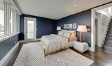 Aside from the beautiful navy blue walls, this bedroom boasts an ensuite and an entrance to a private patio.