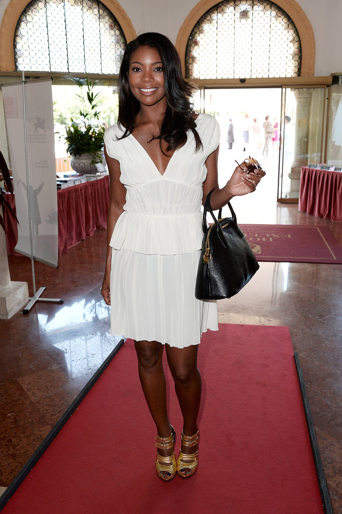 Gabrielle Union helped her little white romantic dress pop thanks to a pair of shiny gold sandals and a black bowler bag at the Venice Film Festival.