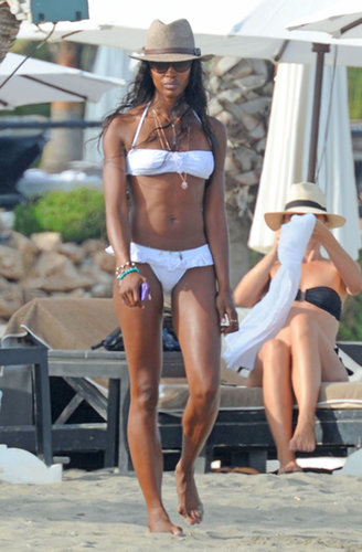Naomi Campbell was fresh in a white ruffled bikini and a bevy of delicate jewels as she walked on the sand in Marbella.