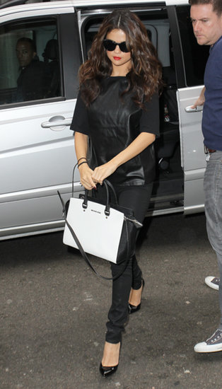 Selena Gomez popped up in London wearing all black, including a leather tee and black patent pumps. She then took her look to on-trend heights thanks to her black and white Michael Kors bag.