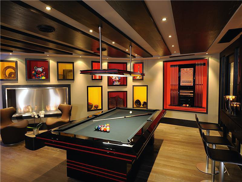With a stainless steel fireplace, sleek pool table, and personal bar, game night just got more competitive.  Source: Sotheby's Realty