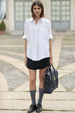 Subvert the schoolgirl look with a white blouse, plain black skirt, and tall socks.