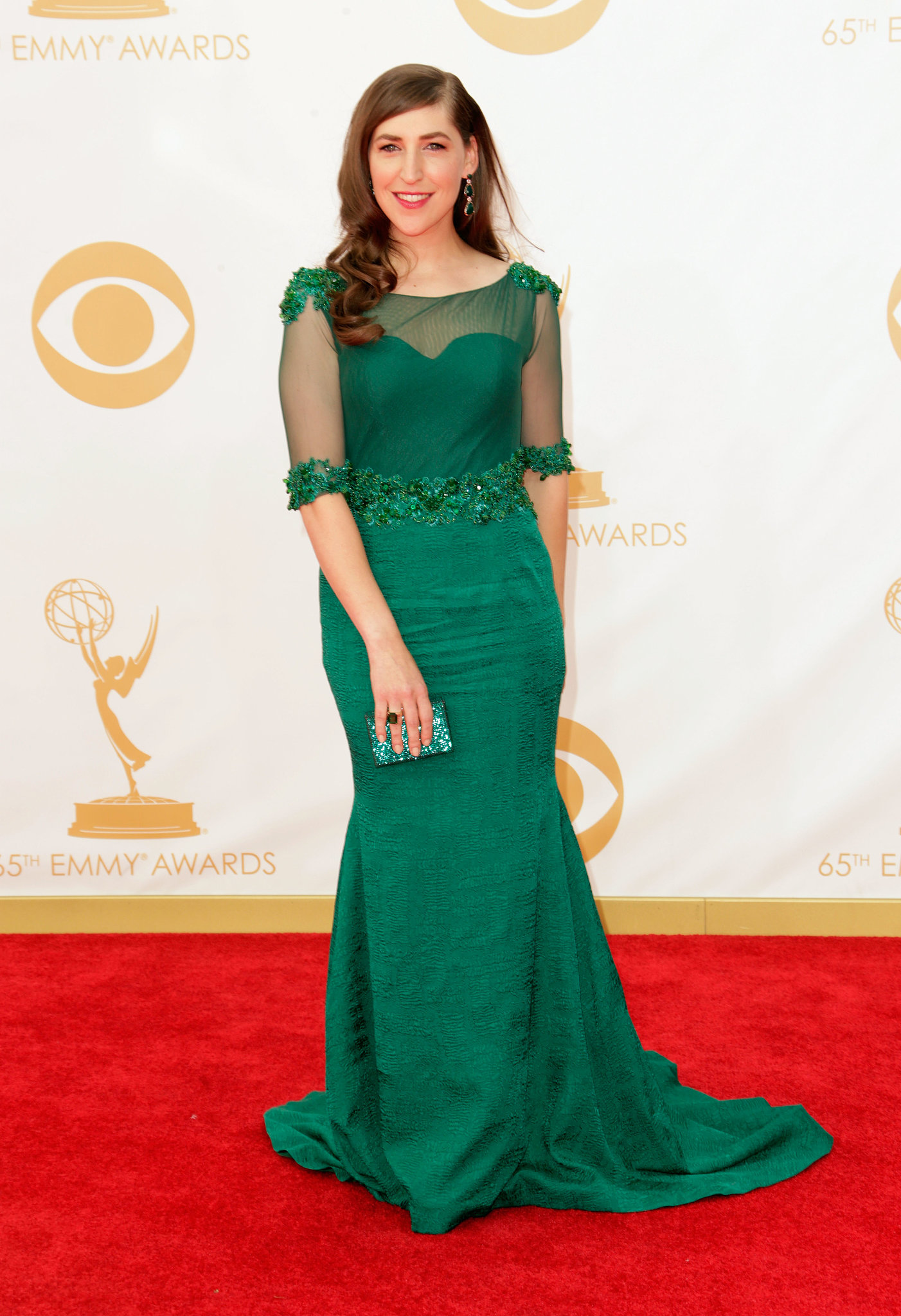 Mayim Bialik glowed in an emerald green Oliver Tolentino Couture gown, with sheer, elb