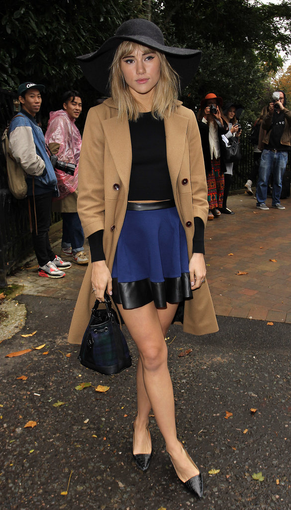 At the Topshop Unique Spring 2014 show, Suki Waterhouse posed in a navy skirt with leather accents, a black floppy hat, and pointy pumps, all by Topshop.