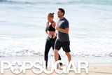 Sam Worthington and Lara Bingle walked on the beach.