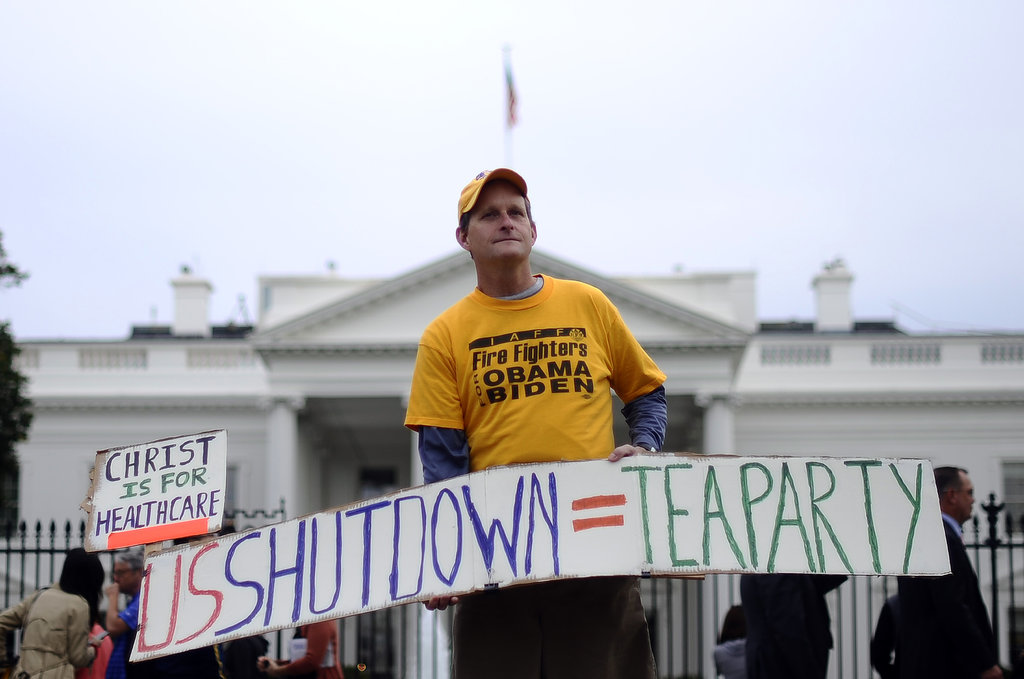 A man held up a sign related to the government shutdown while standing in front of the White House in Washington DC.