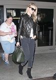 Rosie Huntington-Whiteley amped up her dark ensemble with a black quilted leather jacket while arriving at LAX airport.