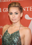 Miley Cyrus traded in her typical red lipstick for the Night of Stars event with shimmering green eye makeup to complement her sequined gown.