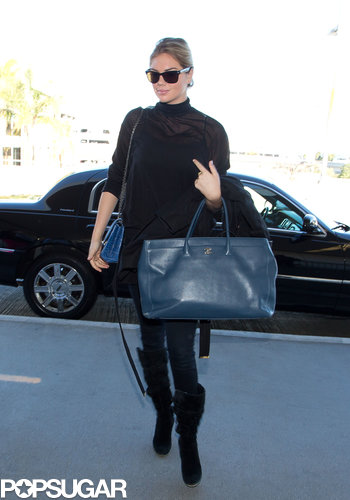 Kate Upton went with all black for her flight, leaning on that gorgeous blue Chanel carry-on for her single spot of color.