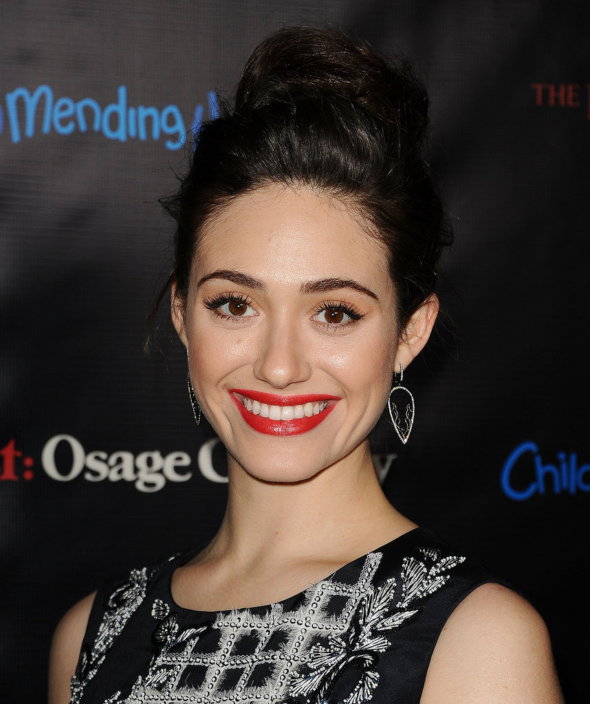 Looking festive in red lipstick and a topknot, Emmy Rossum completed her look with bold brows and winged eyeliner.
