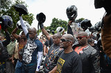 Motorcyclists stopped by the late Nelson Mandela's home, holding up their helmets to pay their respects.
