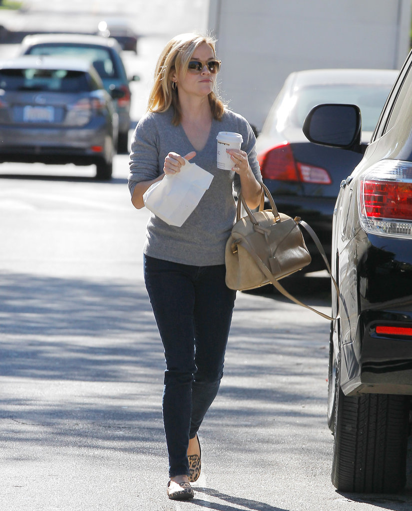 The typically casual Reese Witherspoon chose to accessorize her jeans and sweater combo with a beige bag.