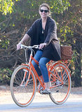 Julia smiled as she rode on an orange bike.