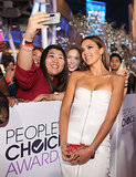 Jessica Alba posed for a fan's picture while walking the red carpet.