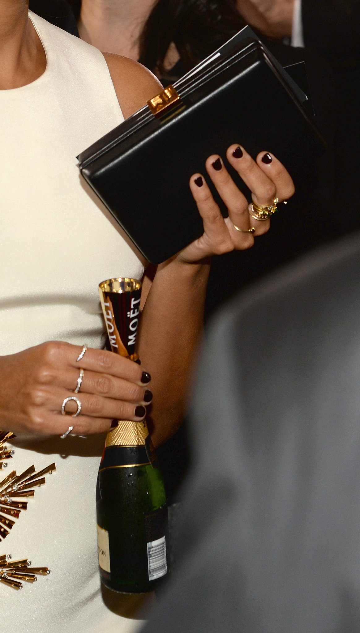 Rashida Jones knows how to accessorize — and we're not just talking about her mini bottle of Moet. The actress added an Ana Khouri gold and diamond Stem ring and black diamond triple Lucky ring, plus an elegant black clutch.