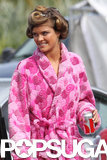 Nina Agdal showed up to set in a bright pink robe.
