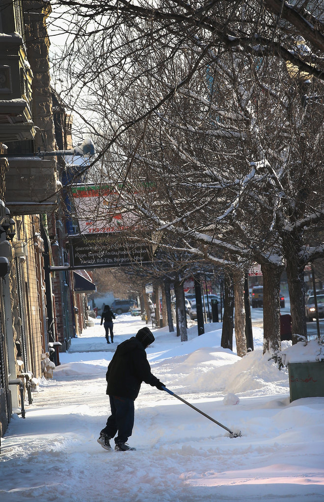 A man cleared snow from the sidewalk in Chicago, where parts of the city saw nearly 12 inches of snowfall overnight.