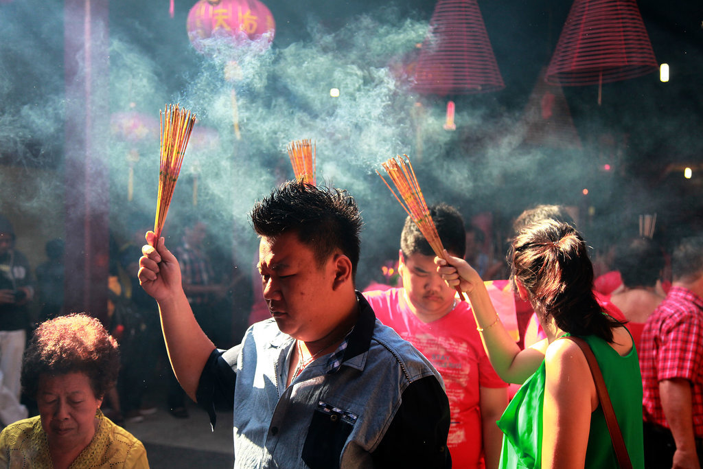 People held up incense sticks during prayer ceremonies in Bali.