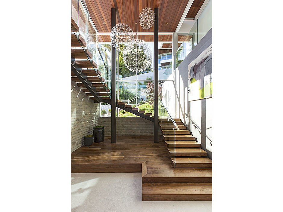 Floating wooden stairs are accented with eye-catching pendant lights. Source: The Agency