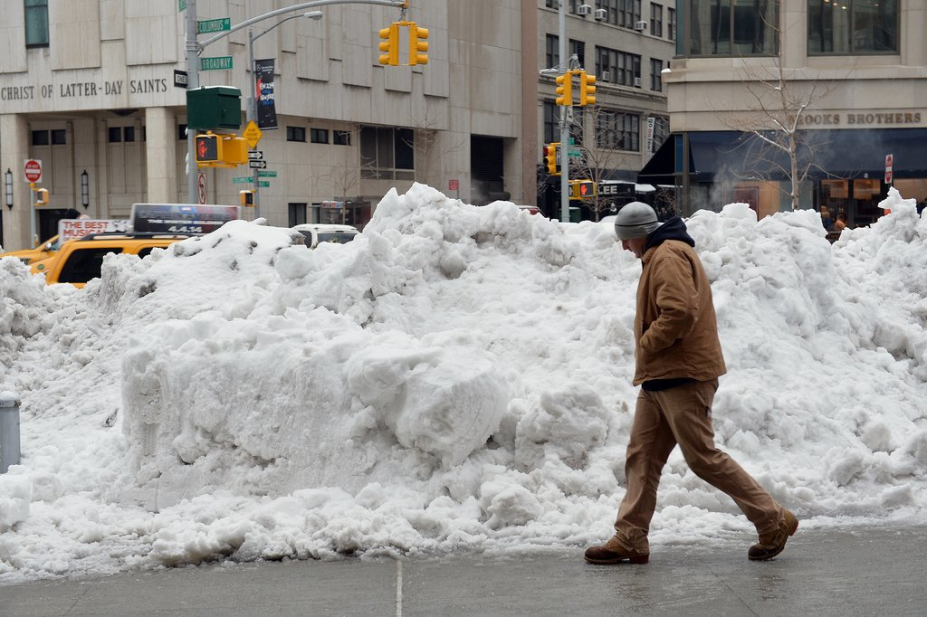 A huge pile of snow sat near the sidewalk in Manhattan.